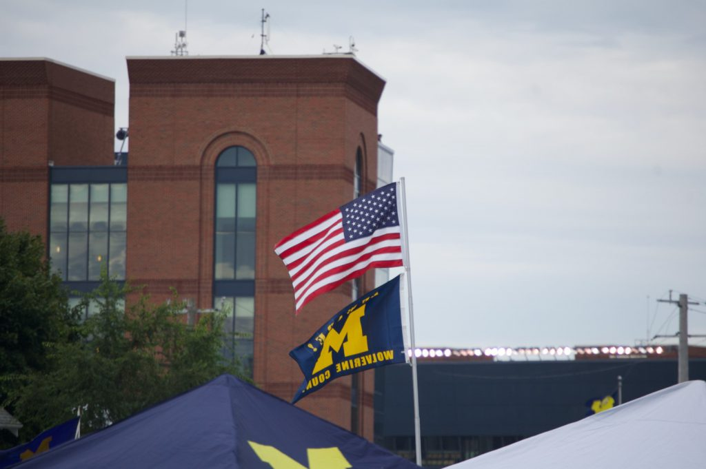 Flags flying with a Michigan Stadium backdrop